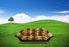 sofa in green grass field - stock illustration