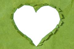ripped  heart in a green paper - stock photo