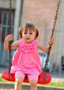 Happy little girl on a swing Stock Photos