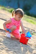 girl playing alone in the sandpit - stock photo