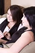 two girls sitting on the sofa watching a movie - stock photo