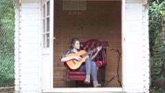 Attractive teenage girl playing acoustic guitar - stock footage