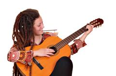 girl with dreadlocks hair play acoustic guitar - stock photo