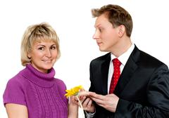 man in suit presents daisywheel to woman - stock photo