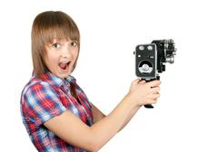 beautiful girl in plaid shirt with movie camera - stock photo