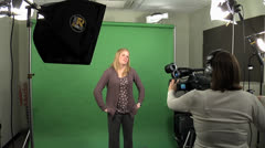 Woman standing in front of green-screen being videotaped. Stock Footage