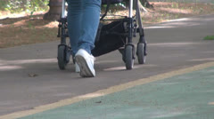 Blue jeans women walks on park with prams Stock Footage