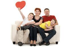 Family of four on a sofa Stock Photos