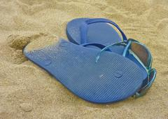 Thongs and a pair of glasses in the sand. Stock Photos