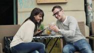 Happy copule with smartphone and tablet in cafe, steadicam shot HD Stock Footage