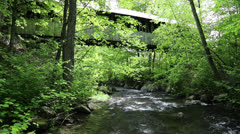 Storm swollen stream running under and covered bridge Stock Footage