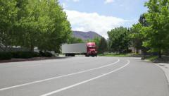 1007 red 18 wheeler pulls out of warehouse area shifting gears - stock footage
