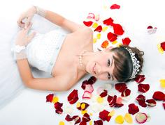 beautiful  bride on  floor among red rose petals - stock photo