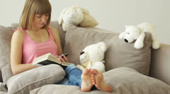 Girl resting on the couch and dials the number. Around stuffed toys Stock Footage
