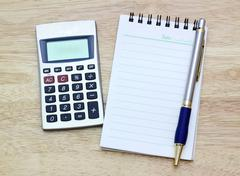 Notebook, silver ballpen and calculator on wooden desk Stock Photos