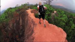 Man running narrow trail wearing backpack in Pai canyon - stock footage