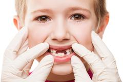 dentist examining child teeth - stock photo