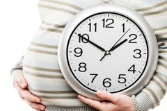 Pregnant woman hand holding large office wall clock showing time Stock Photos