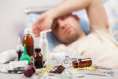 Unwell man patient lying down bed Stock Photos