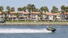 Two Jet Skis Different Directions Waterfront Houses and Boats Stock Footage