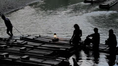 Silhouette people sitting on bamboo river raft being pulled - stock footage