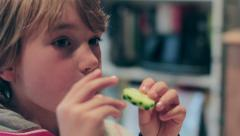 Young cute blonde boy eats pizza with cucumber a la mode Stock Footage
