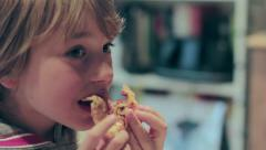 Young hungry cute blonde boy eats pizza quickly Stock Footage