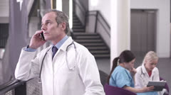 Male doctor talking on mobile phone in hospital Stock Footage