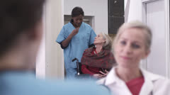 Female nurse pushing patient on wheelchair Stock Footage