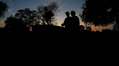 Couple sillouette at cemetery paying last respects Stock Footage