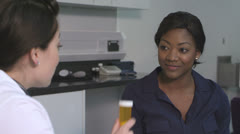 Female doctor giving pill bottle to woman Stock Footage