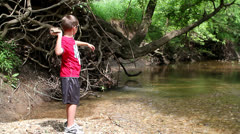 Kid throwing a big rock in to water Stock Footage