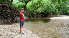 Young boy throwing a big rock into stream Stock Footage