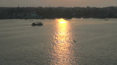 India Kerala Cochin harbor boat enters glowing water at sunset 18 Stock Footage