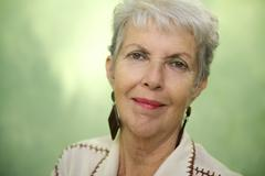 portrait of old caucasian lady looking and smiling at camera - stock photo