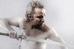warrior man covered in mud with sword - stock photo