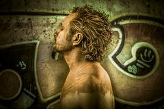 Warrior man covered in mud on grafitti background Stock Photos