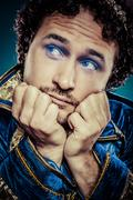 Blue prince dressed with elegant prussian blue jacket, melancholy and sadness Stock Photos