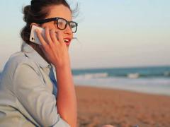 Pretty businesswoman talking on cellphone on the beach NTSC Stock Footage