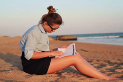 Pretty businesswoman reading documents on the beach NTSC Stock Footage