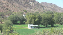 India Rajasthan Udaipur hill behind white house among fields 46 Stock Footage