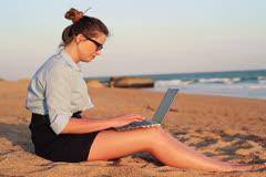 Beautiful businesswoman working on modern laptop on the beach NTSC Stock Footage