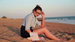 Young sad businesswoman reading documents on the beach HD Stock Footage