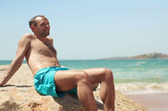 Young happy handsome man relaxing on the beach NTSC Stock Footage