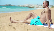 Young happy handsome man relaxing on the beach HD Stock Footage