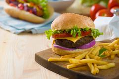 burger with fast food items and materials on the background - stock photo