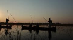 Silhouetted of man on wooden boat in the Okavango Stock Footage