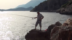 Man fishing from a cliff Stock Footage