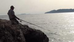 Man sitting and fishing zoom out 2 Stock Footage