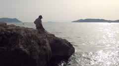 Man sitting and fishing zoom in Stock Footage